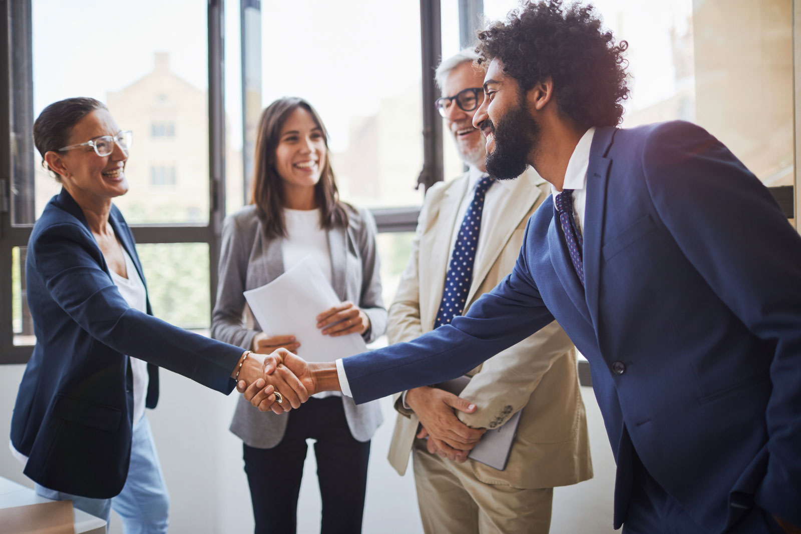 Standing business meeting where man and woman are shaking hands